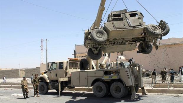 Retirada de un vehículo militar dañado tras el atentado suicida en Afganistán