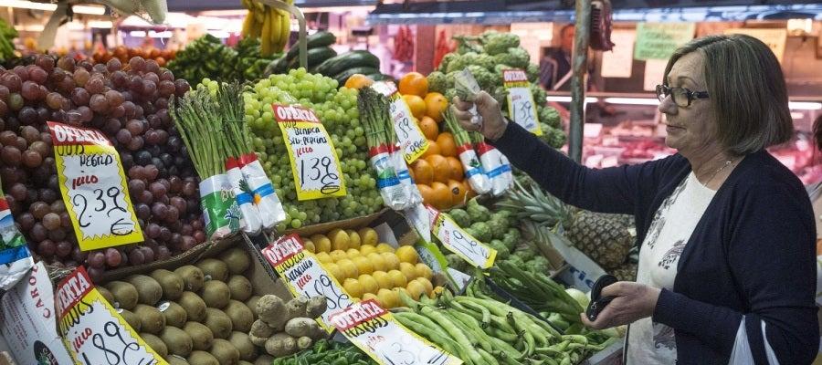 En la imagen, una mujer hace su compra en una frutería del mercado Maravilla en Madrid.
