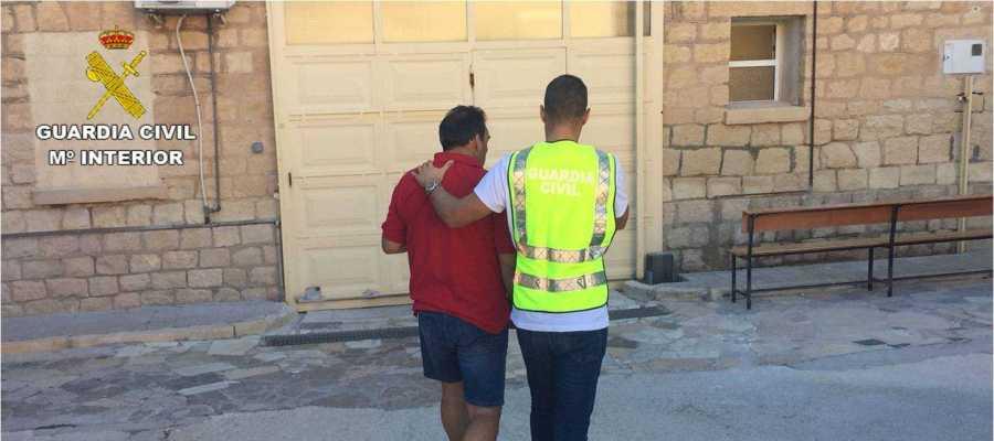 Un agente de la Guardia Civil con el detenido
