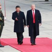 El presidente estadounidense Donald Trump (d) es recibido por su homólogo de China Xi Jinping (c)