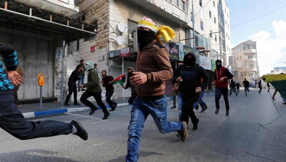 Palestinos corren durante enfrentamientos surgidos entre manifestantes y soldados israelíes