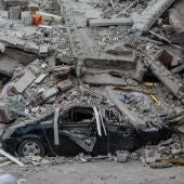 Un trabajador inspecciona un automóvil bajo los escombros de un edificio tras el terremoto de magnitud 7.1 que azotó la Ciudad de México