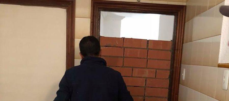 Operario tapia el acceso a una vivienda vacía