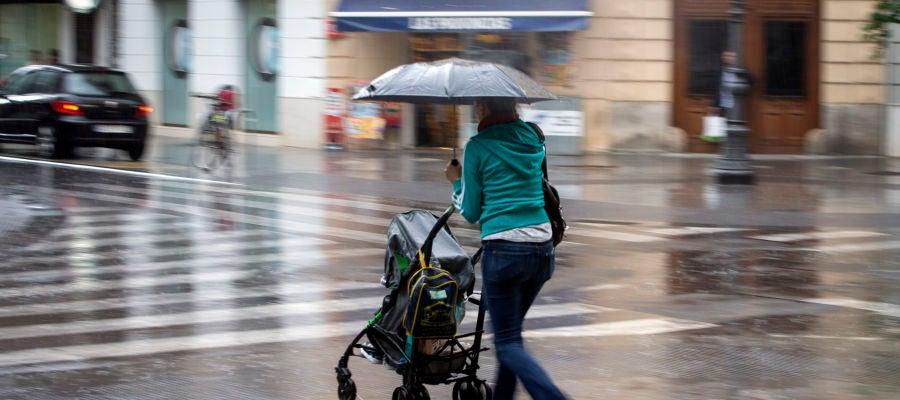 Una mujer con un carrito se protege con un paraguas de la lluvia