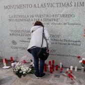 Flores y velas junto al monumento a las víctimas de los atentados del 11M, con motivo del decimocuarto aniversario de la masacre