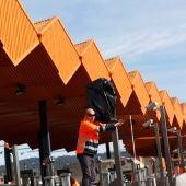 Operarios de autopistas trabajan en quitar las bolsas en las cámaras del peaje de la autopista AP-7