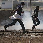 Varios palestinos corriendo durante las protestas en Gaza
