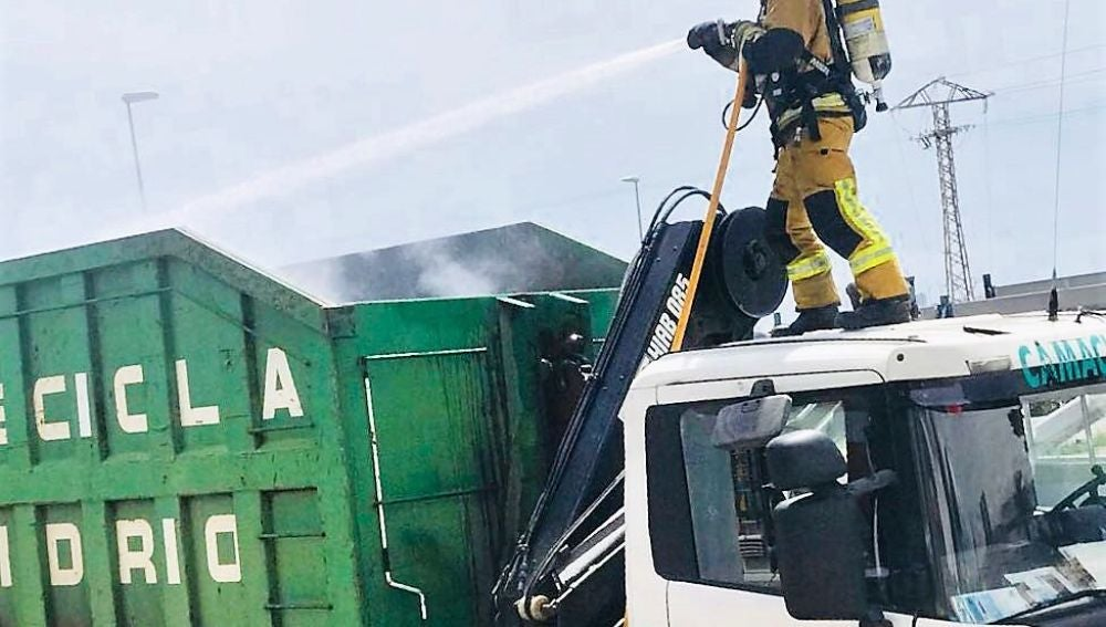 Un bomberos sobre el camión de reciclado incendidado