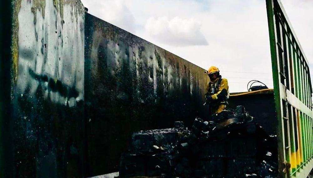 Un bombero en las labores de extinción de las llamadas el camión de reciclaje