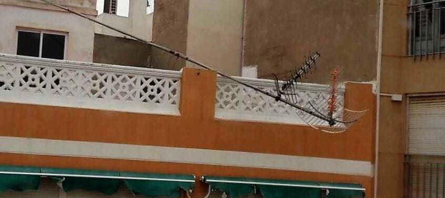 Antena desprendida por el viento en la terraza de un edificio de Elche
