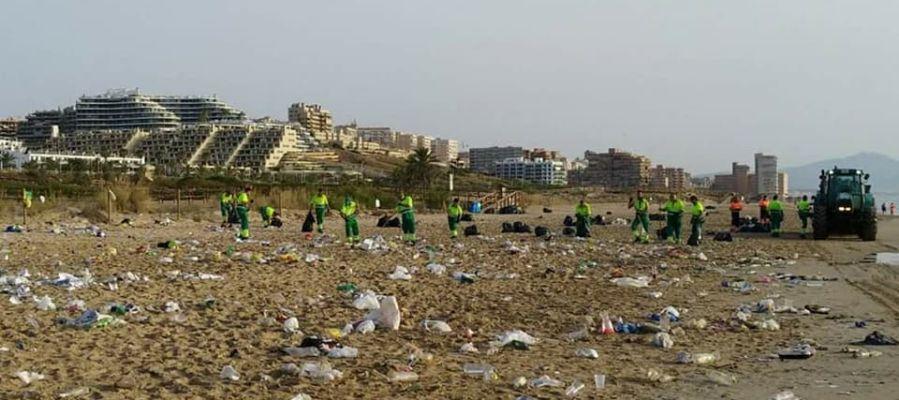 Operarios del servicio de limpieza recogen la basura acumulada en la playa El Carabassí de Elche después de la noche de San Juan.
