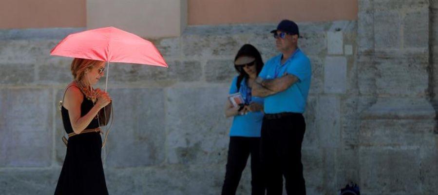 Una mujer se protege del calor con un paraguas