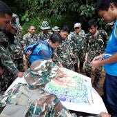 Los equipos de salvamento tailandeses examinan un mapa antes de proceder al rescate de doce niños y un adulto