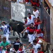 Un toro de Núñez del Cuvillo junto a varios mozos a su paso por la curva de Mercaderes