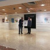 El Dr. Soler y el director de El Corte Inglés de Elche posan junto al cartel ganador