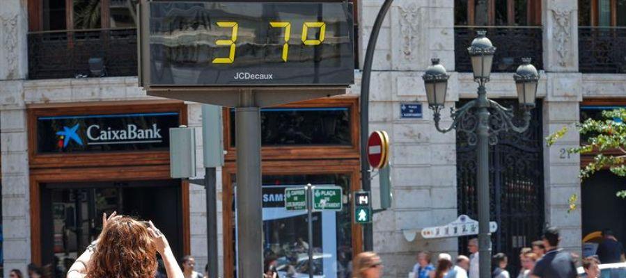 Una mujer toma una fotografía de un termómetro urbano.