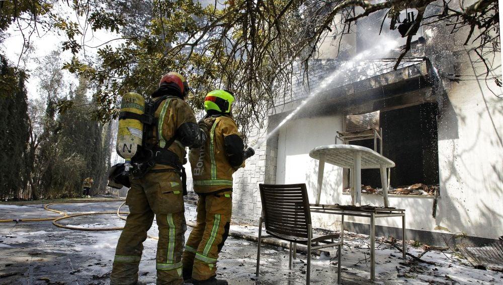 Dos bomberos refrescan el interior de una de las viviendas afectadas por el incendio forestal de Llutxent