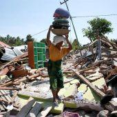 Una mujer carga con sus pertenencias entre los escombros en Lombok (Indonesia) tras el terremoto