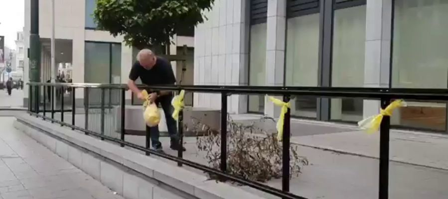 Un operario retira varios lazos amarillos colocados a la entrada del Tribunal belga antes de la vista sobre Llarena