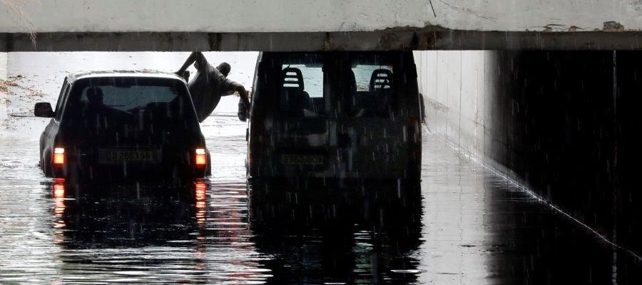 Una persona intenta sale de una furgoneta atrapada en un tunel de Alfafar debido a las intensa lluvias