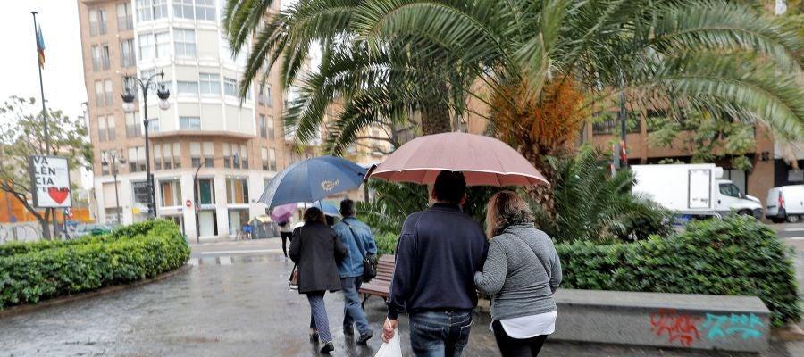 Varias personas pasean protegidas con paraguas