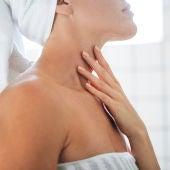 Mujer poniéndose crema en el cuello