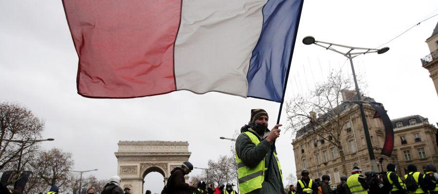 Un manifestante de los chalecos amarillos ondea una bandera tricolora francesa durante una manifestación en París