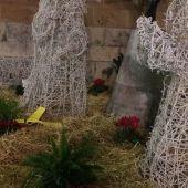 Un lazo amarillo ocupa el lugar del niño Jesús en el Belén municipal.