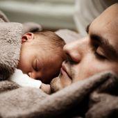 Un padre dormido junto a su bebé