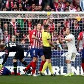 Estrada Fernández muestra una tarjeta amarilla durante el Atlético-Real Madrid