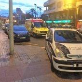 Vehículo de la Policía Nacional y ambulancia junto al edificio de la vivienda asaltada