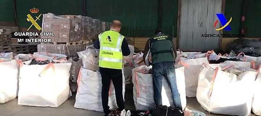 Agentes de la Guardia Civil junto a productos falsificados intervenidos en Elche