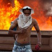 Una persona corre durante enfrentamientos entre antichavistas y miembros de la Guardia Nacional Bolivariana de Venezuela este sábado en el paso fronterizo ubicado en la localidad de Pacaraima (Brasil)