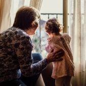 Una abuela mira por la ventana con su nieta