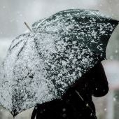 Imagen de archivo de una persona con un paraguas mientras nieva