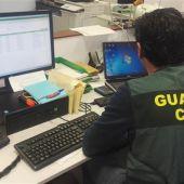 Imagen de archivo de un guardia civil consultando dos ordenadores