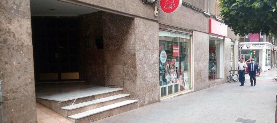 Establecimiento objeto de robo y portal del edificio desde cuyo interior se ha realizado el agujero.