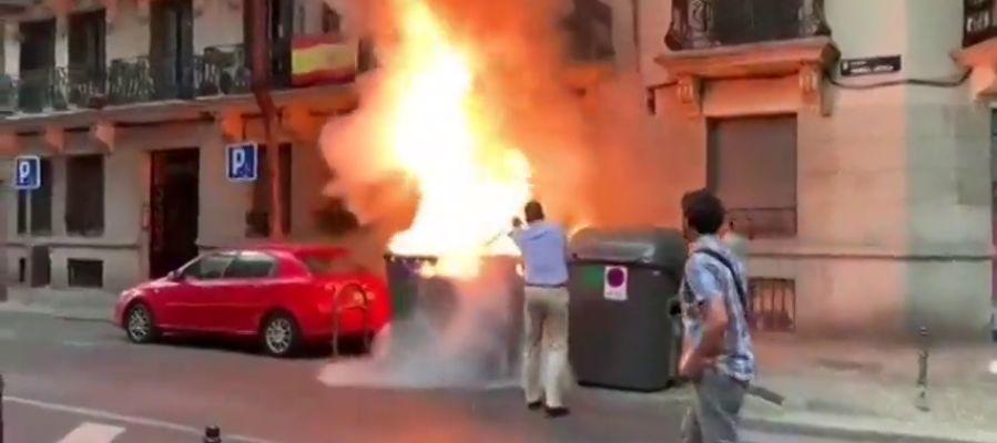 Javier Ortega Smith apaga un contenedor en llamas frente a la sede de Vox en Madrid