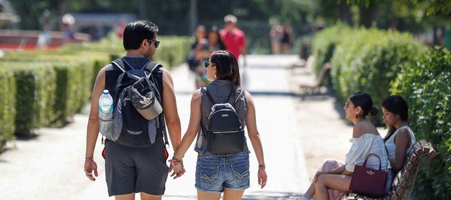 Jóvenes pasean por el parque madrileño de El Retiro