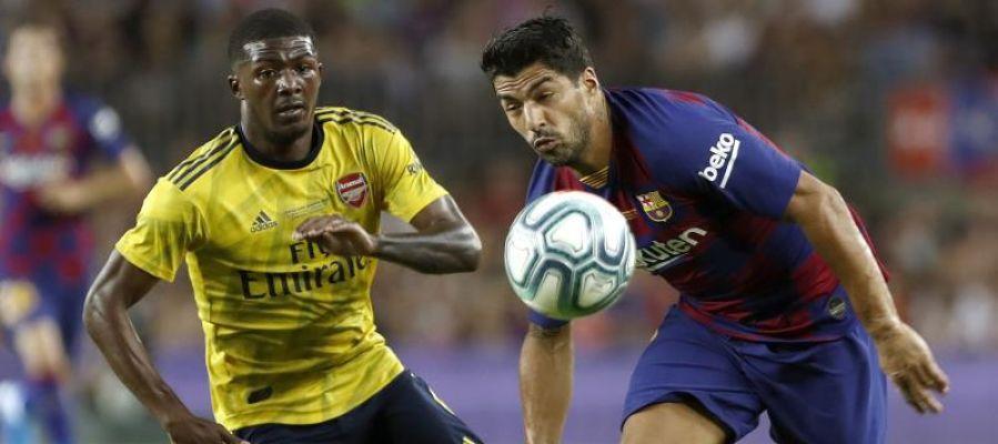 El delantero del FC Barcelona Luis Suárez (d) pelea un balón con Ainsley Maitland-Niles, del Arsenal