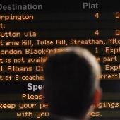Una persona mira los marcadores de una estación en Londres