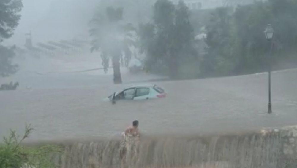 Una mujer sale a nado de su coche, en Cala d'or, atrapado por las fuertes lluvias.