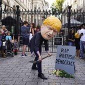 Un hombre vestido con una careta del primer ministro del Reino Unido, Boris Johnson, participa en una protesta frente al número 10 de Downing Street en Londres.