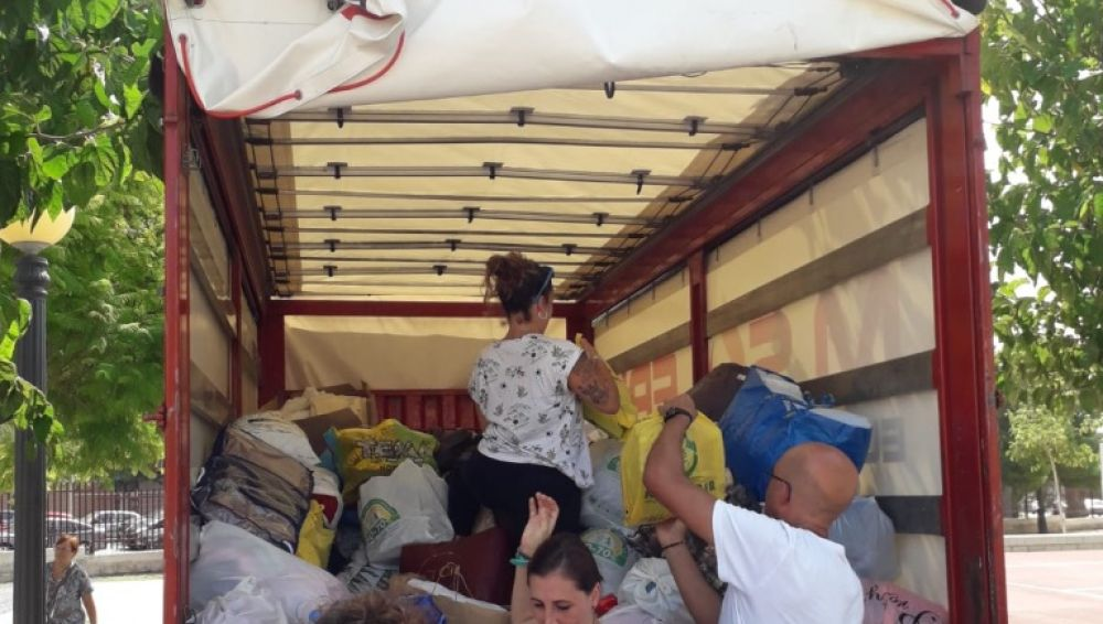 Madres y padres de los colegios Blasco Ibáñez y López Orozco cargan una furgoneta con la ayuda conseguida.