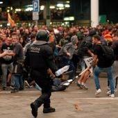 Un mosso d'esquadra durante una de las cargas contra las miles de personas se agolpan ante el Aeropuerto del Prat después de que la plataforma Tsunami Democràtic haya llamado a paralizar la actividad del aeropuerto, en protesta por la condena a los líderes del 'procés'.