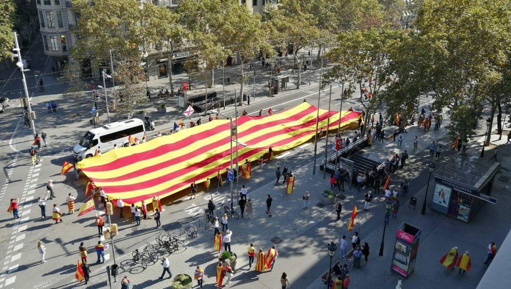 Varias personas portan una gigantesca senyera antes de que comience la manifestación constitucionalista