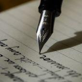 Imagen de archivo de una pluma escribiendo una nota
