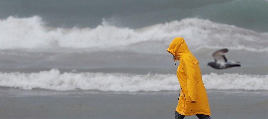 Una persona pasea por la playa de la Malvarrosa bien protegida contra la lluvia