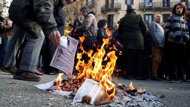Varias personas queman ejemplares de la Constitución española en las calles de Barcelona, con motivo de la celebración del 41 aniversario de la Constitución.