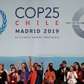 Varios activistas cantan y alzan sus puños después de la sesión plenaria de la Cumbre Climática